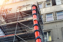 Scaffolding with big red plastic slide chute for rubble debris removal on old historica building facade renewal construction site in city street. Industrial development engineering equipment