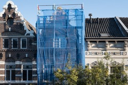 Scaffolding with protective net against historic building to prevent paint and building material from falling on the street and people, during renovation in a street in Maastricht, the Netherlands