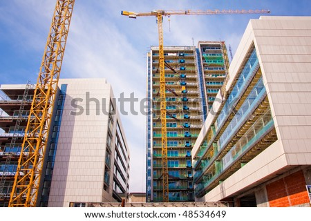 Scaffolds and cranes at buildings construction site