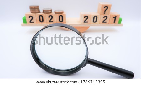Scale comparing 2020 and 2021 financial and investment trends, question on future growth of consumer saving portfolios. Business concept of forecasting recession impact from coronavirus crisis.