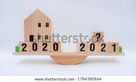 Scale comparing 2020 and 2021 housing market trends, question on real estate economics future plan and property value analysis. Business concept of forecasting financial effect from coronavirus crisis