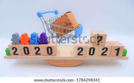 Scale comparing 2020 and 2021 with shopping cart. Online shopping market analysis concept, Question on future consumer volume and e-commerce marketing trends, economic impact from coronavirus crisis. Photo stock ©