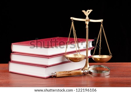 scale of justice on wooden table and black background