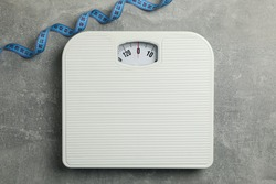 Scales and measuring tape on gray background. Weight loss concept