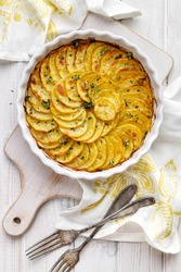 Scalloped potatoes, potato casserole with the addition of aromatic herbs  in a ceramic baking dish, top view