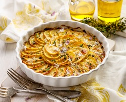 Scalloped potatoes, potato casserole with the addition of herbs and edible chives flowers in a ceramic baking dish