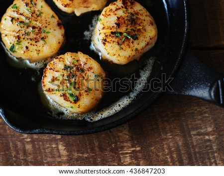Scallops being cooked in a small cast iron pan. Shown on redwood background.