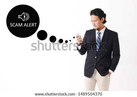Scam Alert concept with young man holding smartphone on white background #1489504370