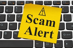 Scam Alert media message on yellow sticky note on a black and silver keyboard