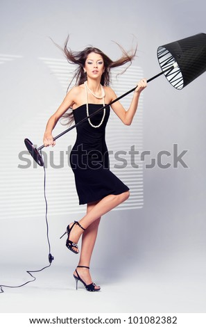 scandalous woman in a black dress with a white floor lamp next