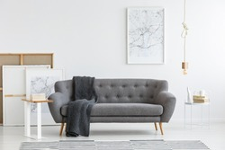 Scandi living room interior with grey, big sofa in the center and modern picture on the wall