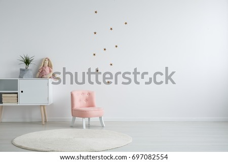 Scandi style girl's bedroom with a plant standing on a white cupboard next to a pink, chic chair, and a white circular carpet