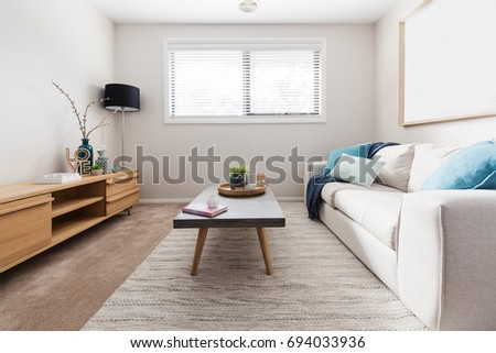 Scandi style living room interior with teal accent cushions #694033936