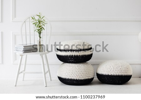 scandinavan modern interior. white wooden chair in white room. houseplant on a stool. black and white woven pouffes
