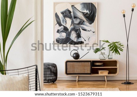 Scandinavian and design home interior of living room with wooden commode, design black lamp, rattan basket, plants and elegant accessories. Stylish home decor. Template. Mock up poster paintings.