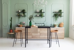 Scandinavian classic kitchen with wooden decor and green plants, minimalistic interior design. Real photo. Eco home decor.