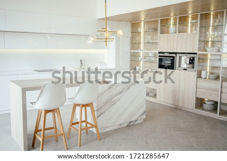 Scandinavian empty classic modern luxury kitchen with wooden, white, marble details, new stylish furniture, minimalistic nordic interior design.  Bar stools, glass display rack, dishes and glassware