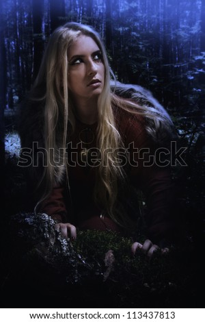 Scandinavian girl in the night dark forest