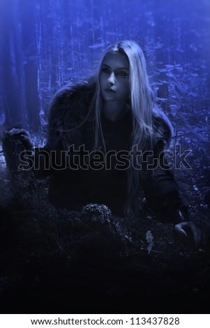 Scandinavian girl in the night dark forest
