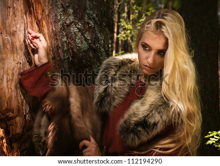 Scandinavian girl with runic signs holding a fur skins