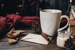 Scandinavian hygge styled Christmas composition. Cozy winter homely scene with books, cup of tea or coffee, cookies, cinnamon sticks and knitted things. Santa Claus working place. Flatlay. Home decor.