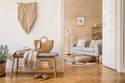 Scandinavian interior of open space with wooden bench, grey sofa, pillows, palid, mock up picture frame, macrame, plant, books, carpet, decoration and elegant personal accessories in home decor.