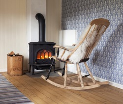 Scandinavian interior: wood burning stove, box of firewood and old restored rocking chair in living room corner. Rag carpet on oiled wooden floor. White sheep skin in rocking chair.