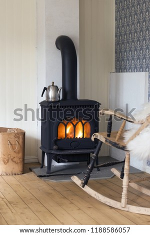 Scandinavian interior: wood burning stove, box of firewood and old restored rocking chair in living room corner. Metal coffeepot at stove. White sheep skin in rocking chair. Oiled wooden floor.  - Shutterstock ID 1188586057