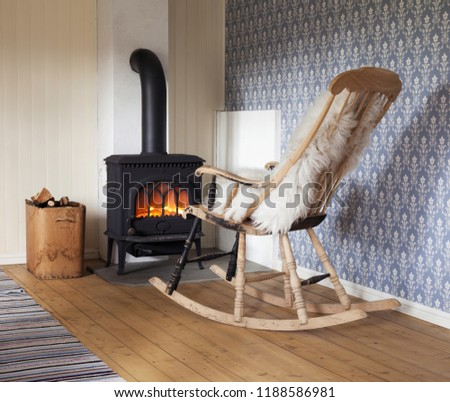 Scandinavian interior: wood burning stove, box of firewood and old restored rocking chair in living room corner. Rag carpet on oiled wooden floor. White sheep skin in rocking chair.  Stock fotó ©