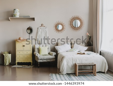 Scandinavian modern cozy interior. Wide bed with pillows, armchair and decorations in bedroom. Real photo #1446393974