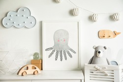 Scandinavian newbornbaby shelf with mock up photo frame, wooden accessories, toys, teddy bear and hanging cloud. White and cozy childroom.