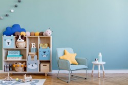 Scandinavian nursery room with wooden cabinet, mint armchair, natural teddy bears and plush animal toys. Cute modern interior of playroom with eucalyptus walls, baby accessories and toys. Copy space.
