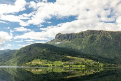 Scandinavian perfect landscape. Norwegian landscape with a fjord, mountains and a village. Summer idealistic landscape. Village by the sea.
