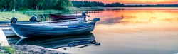 Scandinavian white night in Sweden. Close view at motor boats at lake. Midnight Sun just below horizon line, golden sun rays illuminate highest clouds in atmosphere. Lake and forest at coast line