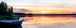 Scandinavian white night in Sweden. View at midnight Sun just below horizon line, golden sun rays illuminate highest clouds in atmosphere. Lake and forest at coast line. Blurry close view at boats