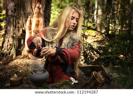 Scandinavian witch pythoness cooking potion in a dark forest