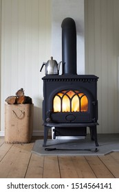 Stock photo of Scandinavian-style wood burning stove and box of firewood  in living room, metal coffeepot on stove.