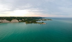 Scarborough Bluffs aerial panorama shot from above with drone, one of the Toronto city attractions. Summer day, high white clay cliffs and turquoise water of Lake Ontario. Wide angle shot.