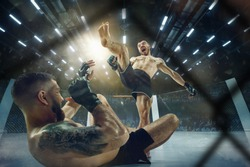 Scare of death. Two professional fighters posing on the sport boxing ring. Couple of fit muscular caucasian athletes or boxers fighting. Sport, competition and human emotions concept.