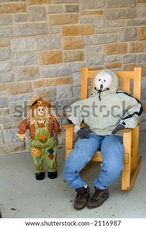scarecrow and puppet sitting in the chair