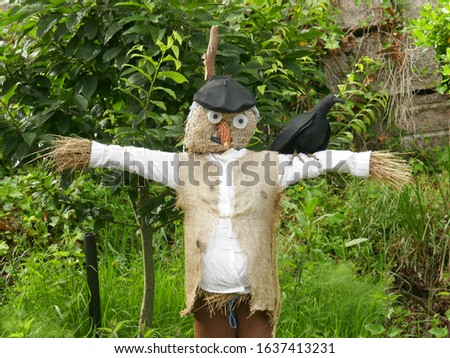 Scarecrow made of hay, with burlap vest, corn nose a beret and crow on shoulder standing in a garden