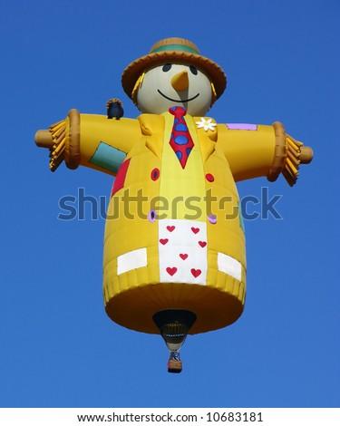 Scarecrow shape hot air balloon over a blue sky