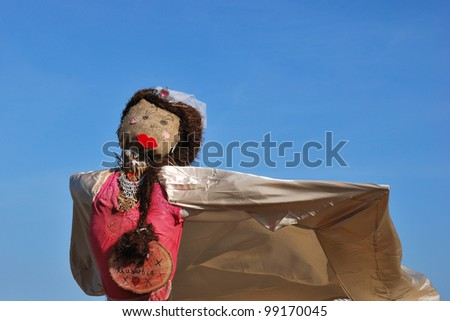 scarecrow with cape and blue sky