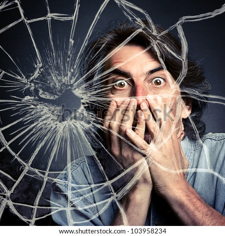 scared adult man with hand covering mouth and broken glass.