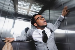 scared african american businessman with paper bag suffering from panic attack in elevator