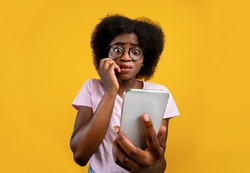 Scared african american woman holding mobile phone seeing bad news, photos or message and looking at camera over yellow background. Human reaction, expression