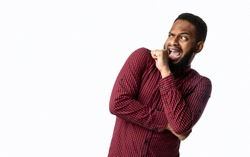 Scared Black Man Looking Aside In Fright Standing Over White Background. Frightened African Guy Posing In Studio. I'm Afraid Of This Concept, Advertisement Banner. Empty Space For Text