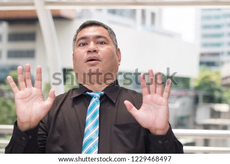 scared business man saying no. portrait of excited, scared asian businessman showing stop, halt hand gesture with fear. 50s old southeast asian man model