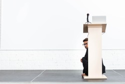 scared businessman in glasses hiding behind podium tribune during conference isolated on white