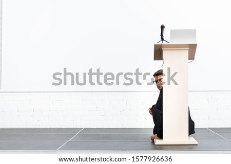 scared businessman in glasses hiding behind podium tribune during conference isolated on white  Foto stock ©